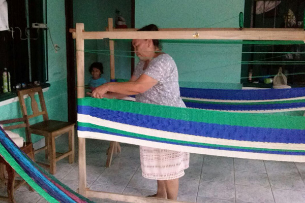 Artisan Weaving Campesino Hammock While Child Looks On